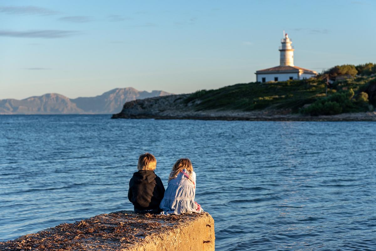 Siblings and the lighthouse. Family photoshoot at Alcanada Beach Park. Mallorca. Balearic Islands.