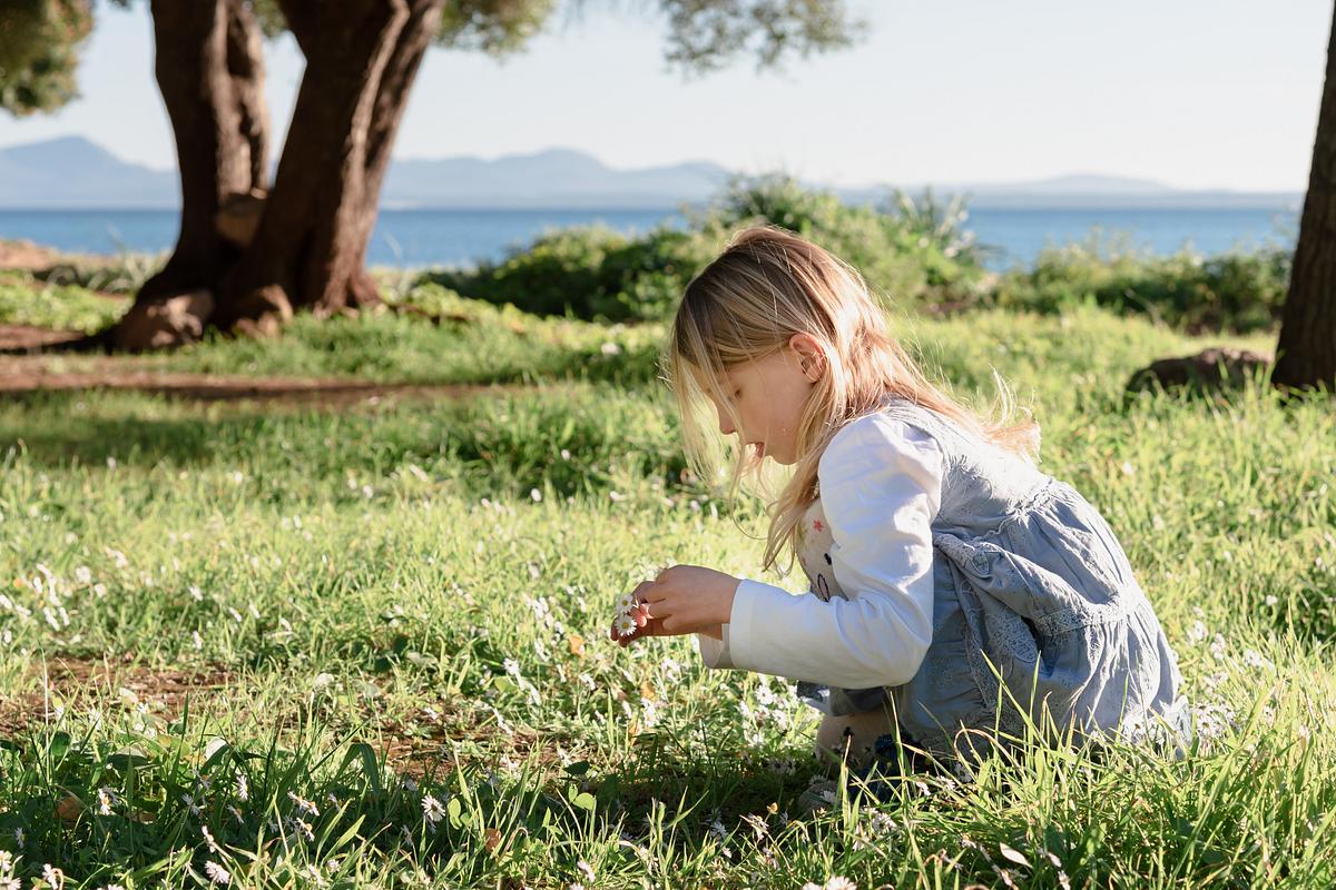 Picking up white flowers. Family photoshoot at Alcanada Beach Park. Mallorca. Balearic Islands.