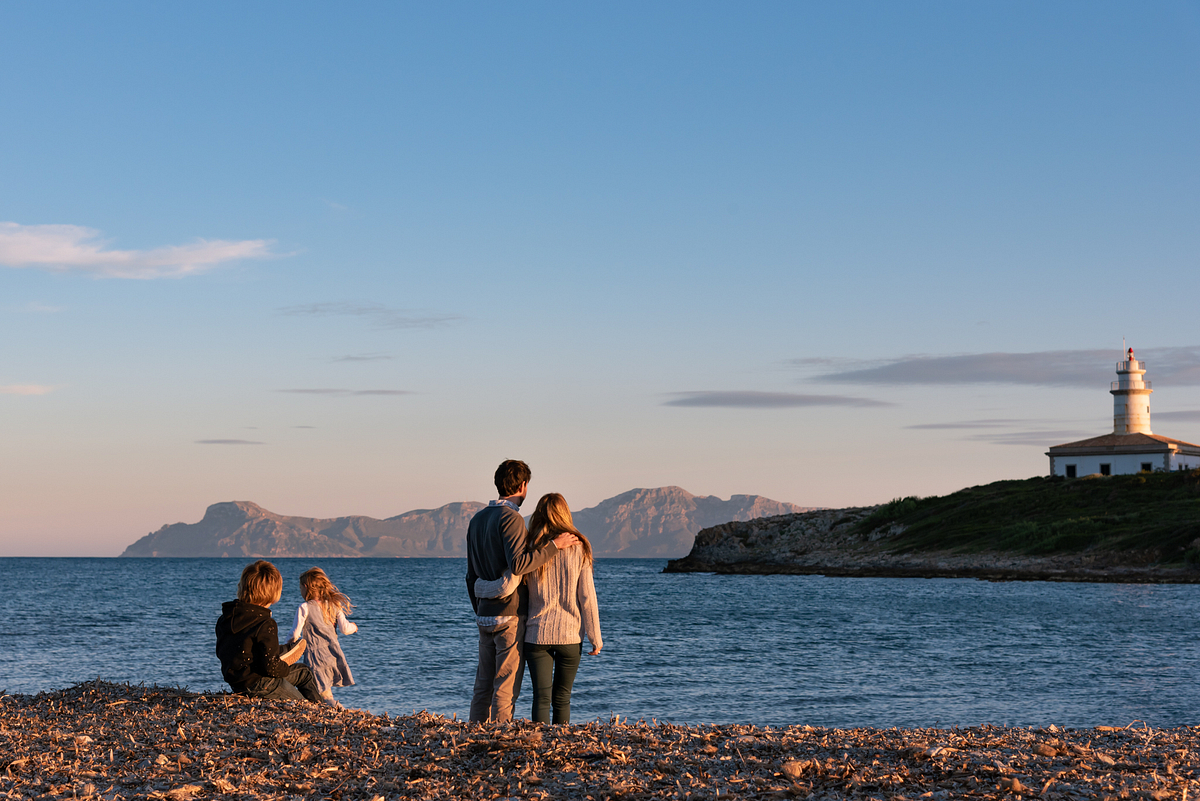 All together and the views. Family photoshoot at Alcanada Beach Park. Mallorca. Balearic Islands.