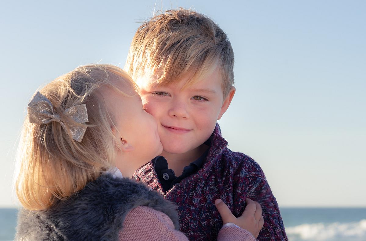 Little sister kiss. Family photoshoot at the beach. Palma de Mallorca. Balearic Islands.