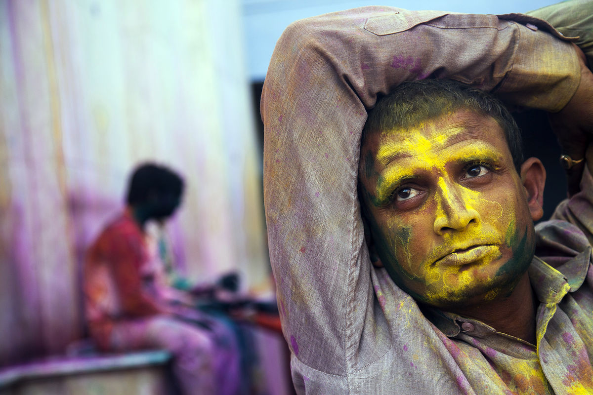 An indian pilgrim with face painted with colours looks on the occasion of holi, festival of colours in Nandgaon village, in Mathura District, Uttar Pradesh India.