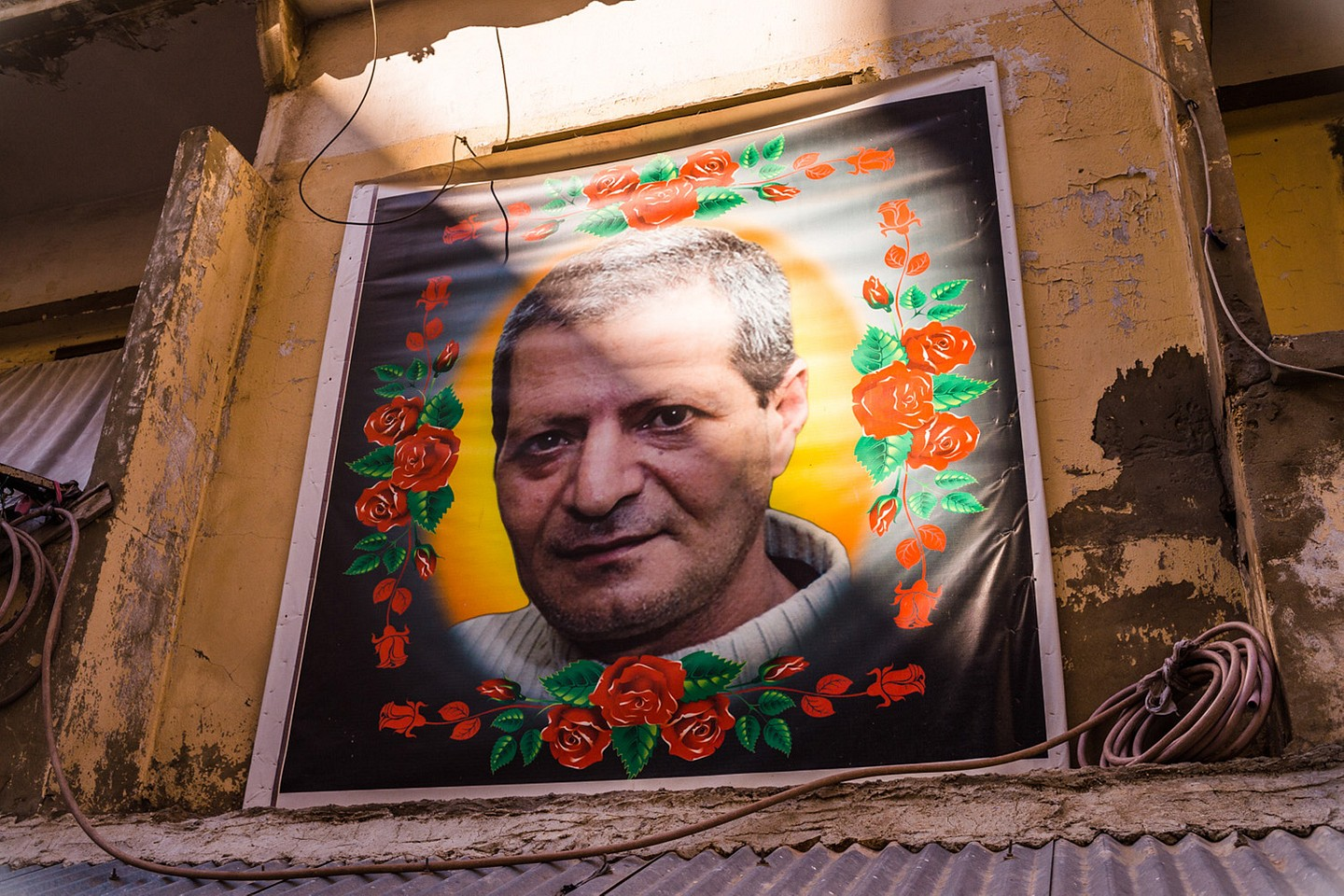 The portrait of Mahmud Hussein Hassan, a Jabal Mohsen resident, decorates the entrance of a residential building. Mr. Hassan died when he tried to prevent one of two suicide bombers from detonating their explosives. The double suicide bombing targeted a Jabal Mohsen coffee house and killed nine people. It was carried out on January 9, 2015, by two Lebanese men associated with the Al-Nusra Front, a Sunni radical group.