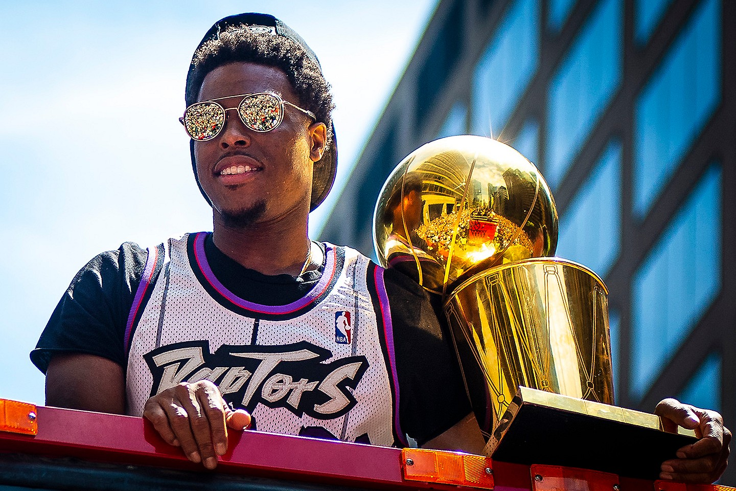 The crowd is reflected in Toronto Raptors point guard Kyle Lowry's sunglasses as he holds the Larry O'Brien NBA Championship Trophy during the 2019 Toronto Raptors Championship parade, Toronto, Monday, June 17, 2019. The Raptors became the first non-American team to win an NBA title after defeating the Golden State Warriors 4–2.