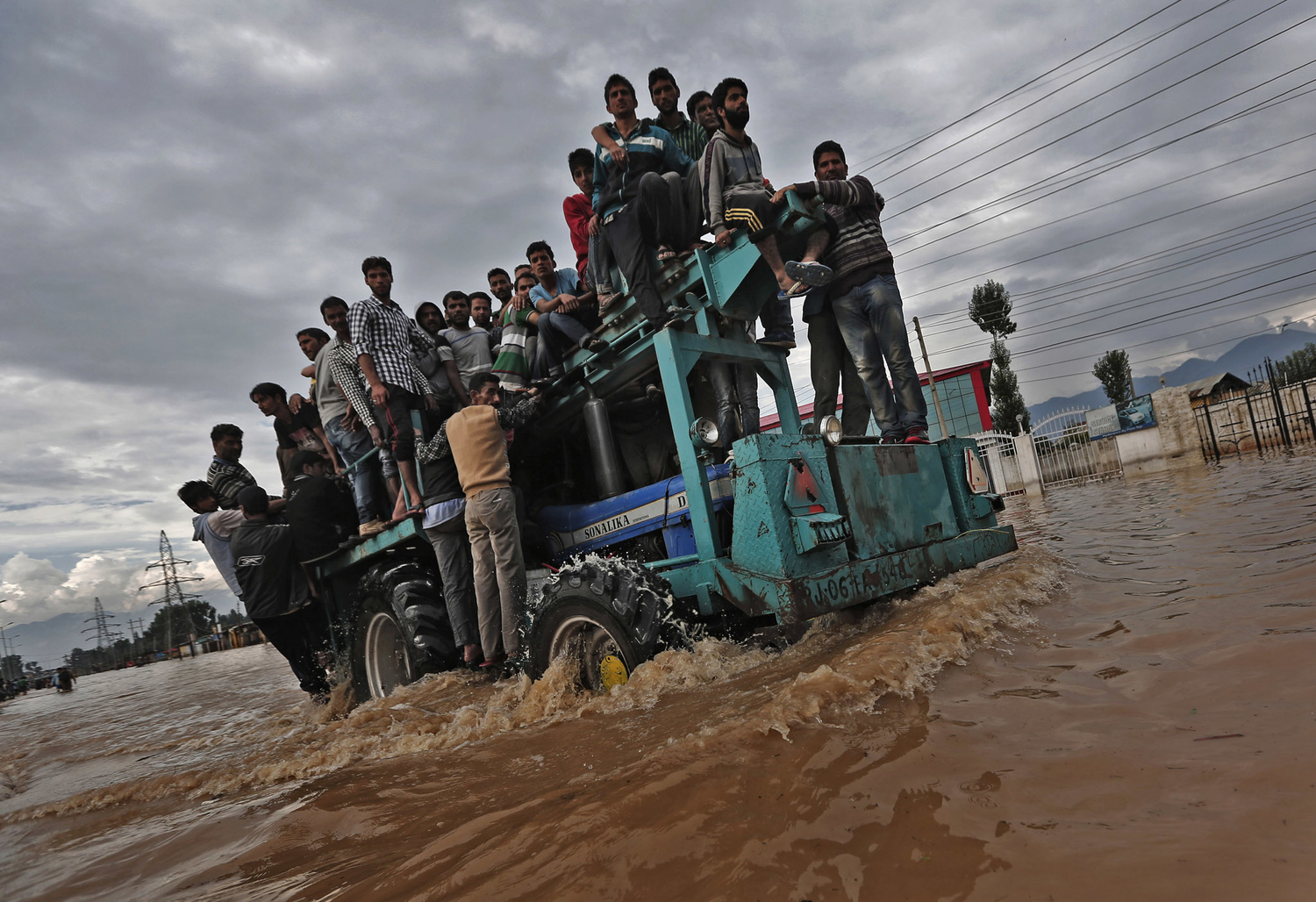 A tractor evacuating Kashmiri flood victims to higher grounds, travels through a flooded street in Srinagar