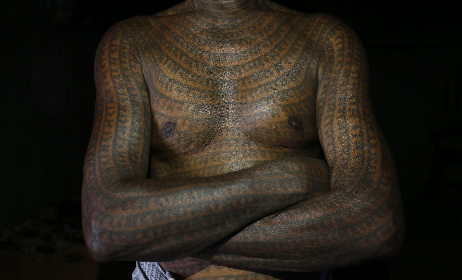 Tandon a follower of Ramnami Samaj who has tattoos God 'Ram' name on his full body poses for a picture inside his house at the village Jamgahan