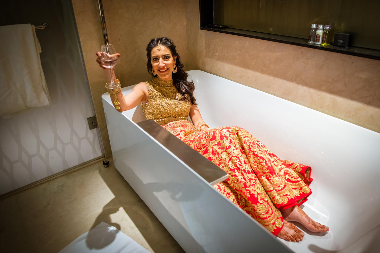 unique bridal portrait in a bathtub of 5star hotel sipping wine