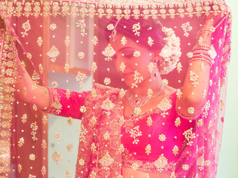 bride in veil pink lehenga