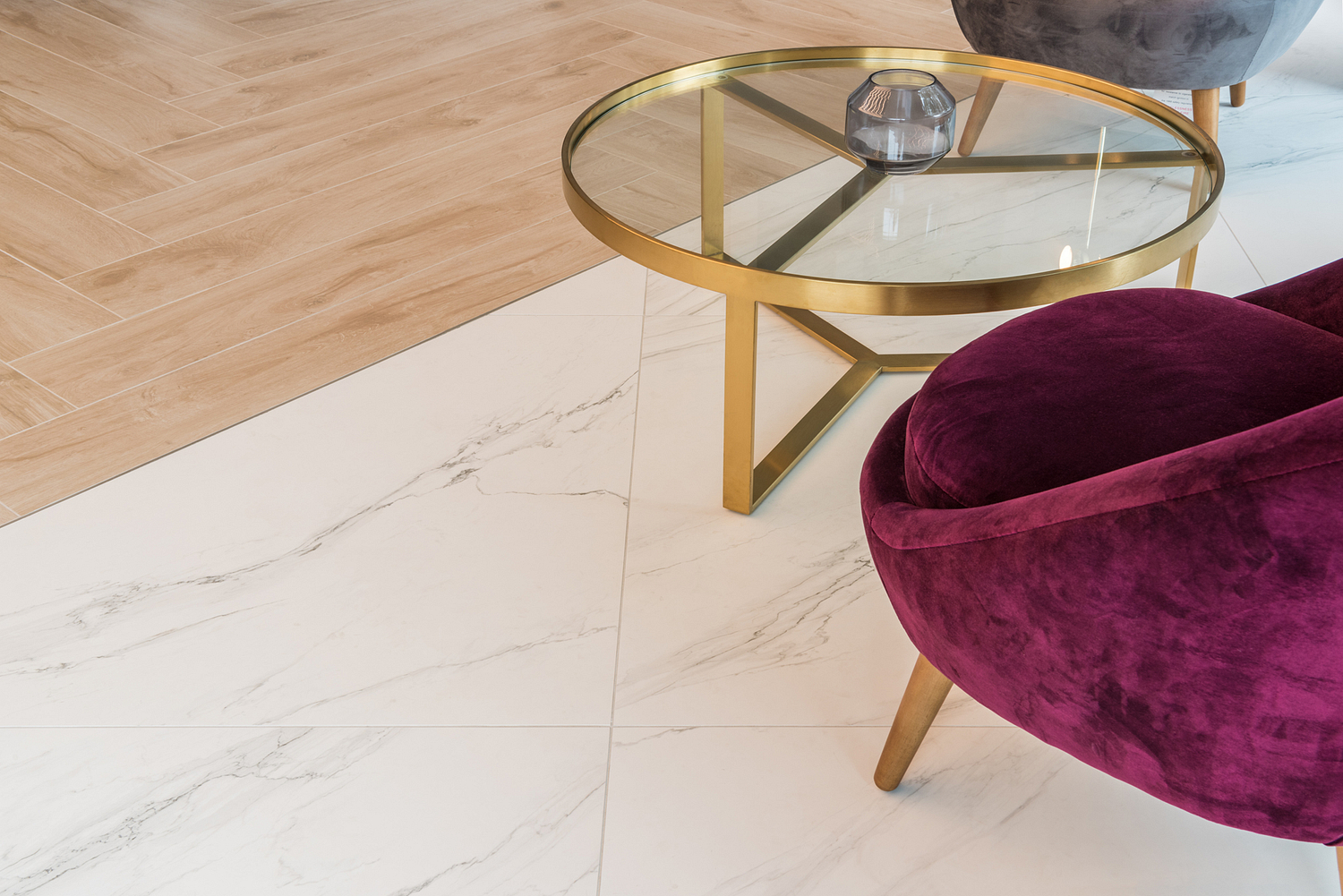Wood and tile flooring contrasts with brass table detail, London