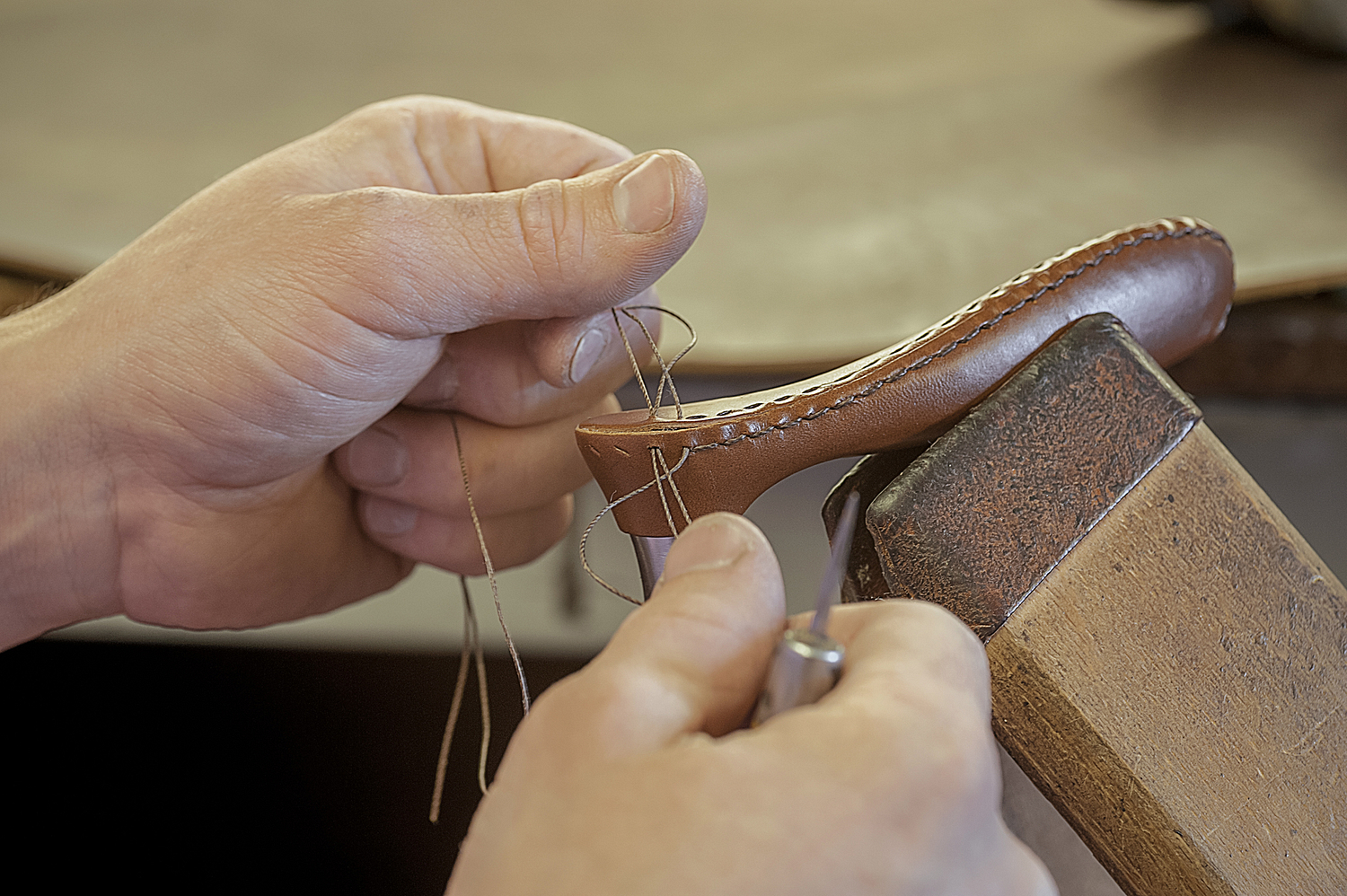 Leather stitching detail with hands, Oxford