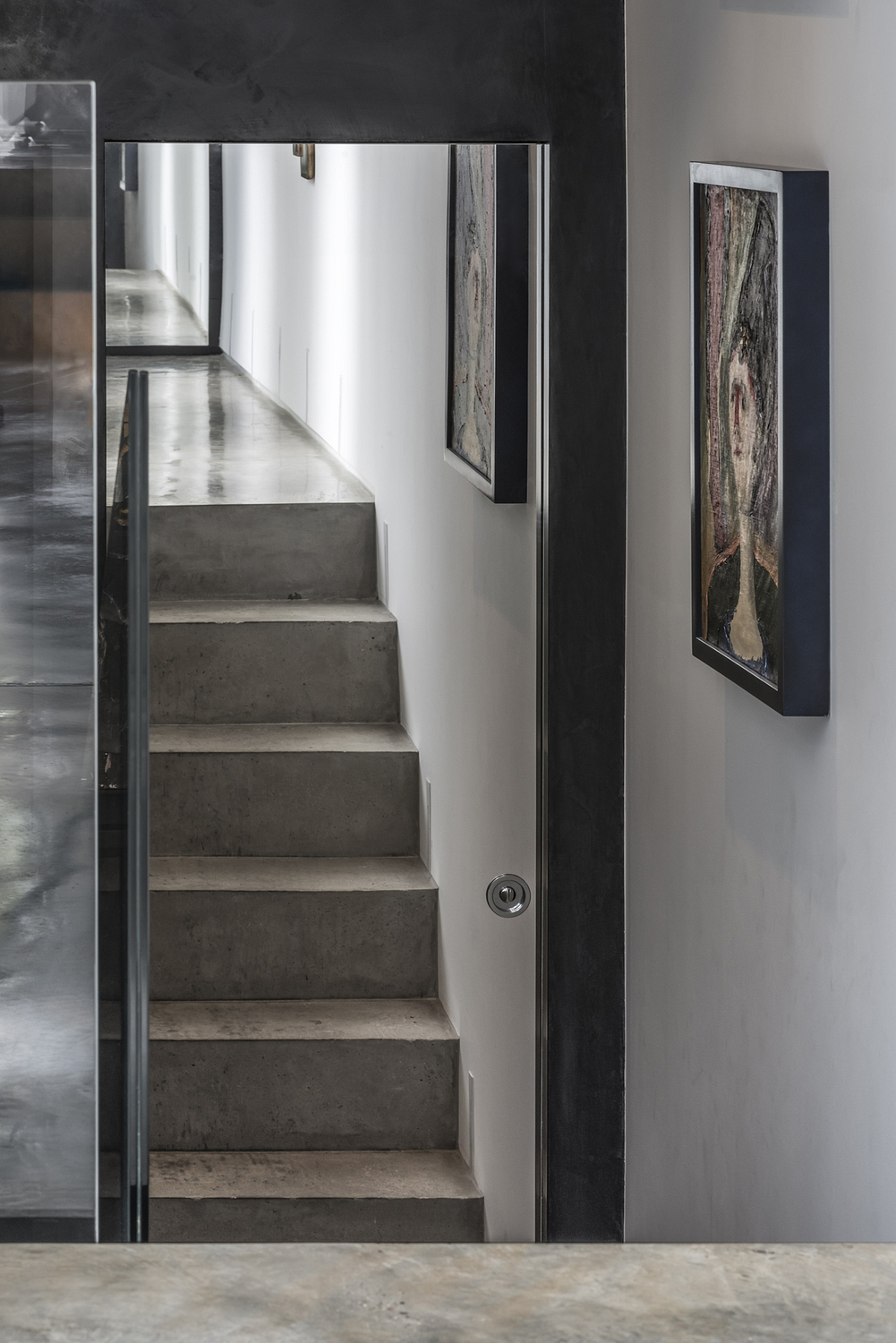 Mirrored door reflecting polished concrete stairs