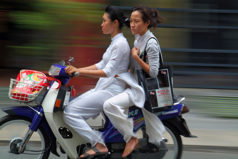 Schoolgirls in Ao Dai on Motorbike in Ho Chi Minh City, Vietnam