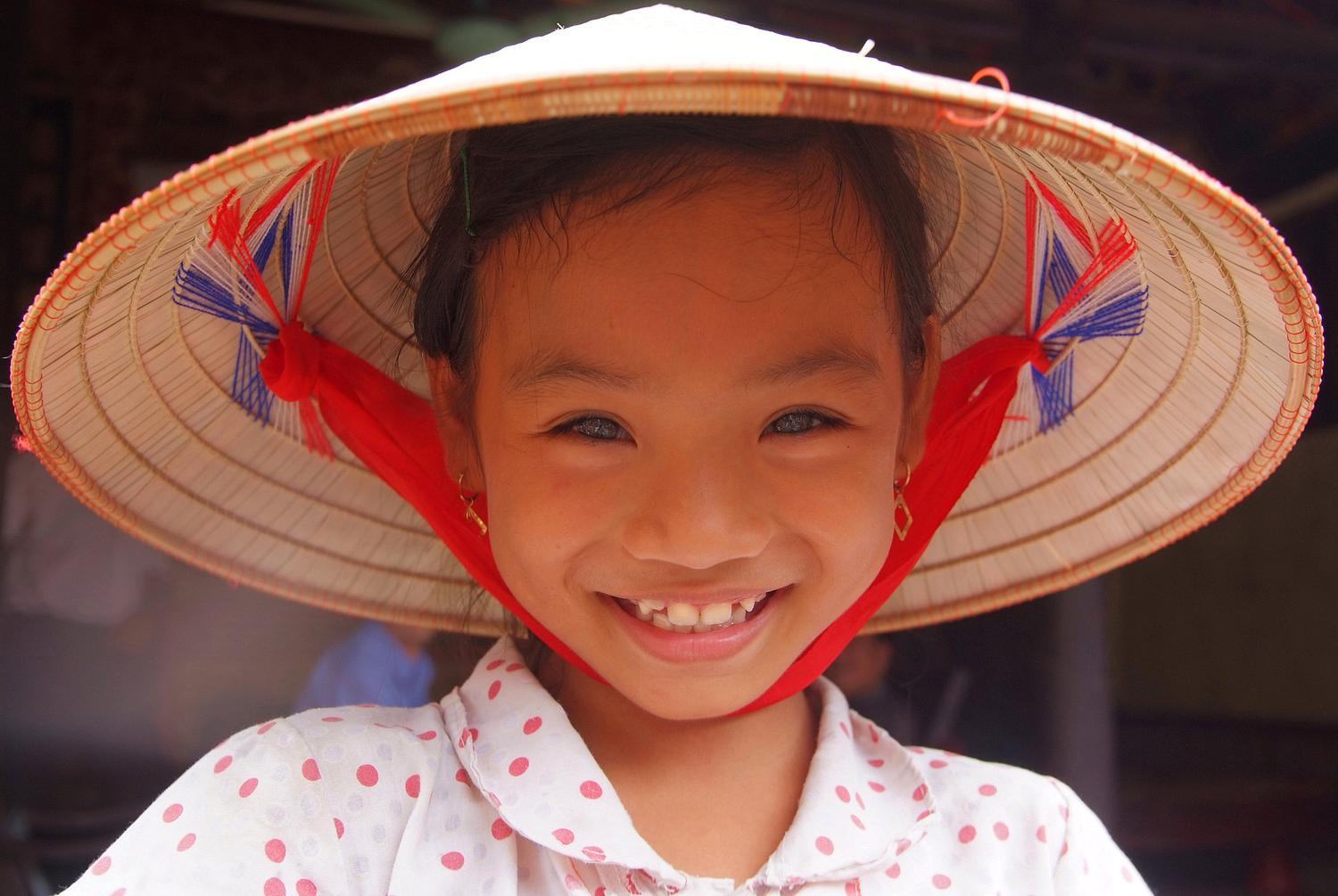 Portrait of a Smiling Girl in a Vietnamese Conical Hat