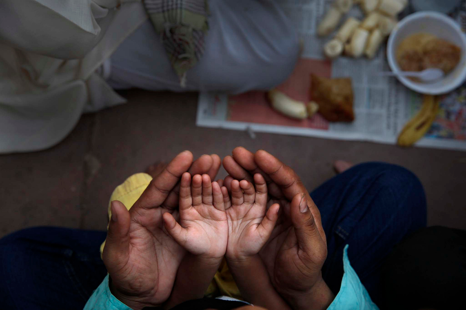An Indian Muslim father holds the hands of her daughter in his palms and prays before opening the fast in the evening on the first day of the Ramadan at the Jama Maszid or Mosque, in  New Delhi, India ,Monday, June 30, 2014. (AP Photo /Manish Swarup)