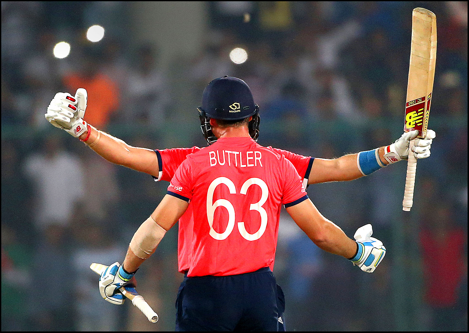 England's Jos Buttler, and teammate Joe Root, face hidden, celebrate after defeating New Zealand during their ICC Twenty20 2016 Cricket World Cup semifinal match at the Feroz Shah Kotla Cricket Stadium in New Delhi, India, Wednesday, March 30, 2016. England win by seven wickets.