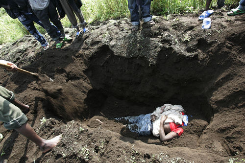 Displaced people bury one of three teenage boys in a cabage field next to the road after they were killed when an army tank run over them as they were fleeing fighting, Sunday, Oct. 26, 2008 near Kibumba some 40 kilometers north of Goma in eastern Congo.
