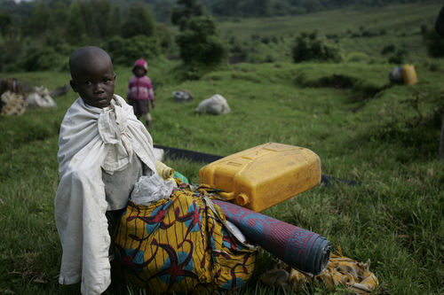 A young girl rest next to the road as peole flee fighting, Sunday, Oct. 26, 2008 near Kibumba some 40 kilometers north of Goma in eastern Congo