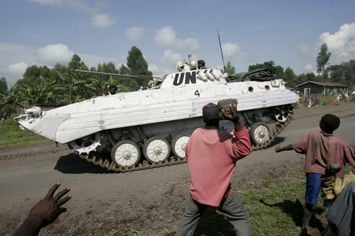 People stone United Nations peacekeepers in a tank as they pass through the village of Kibati some 12 kilometers north of Goma in eastern Congo, Tuesday, Oct. 28, 2008.