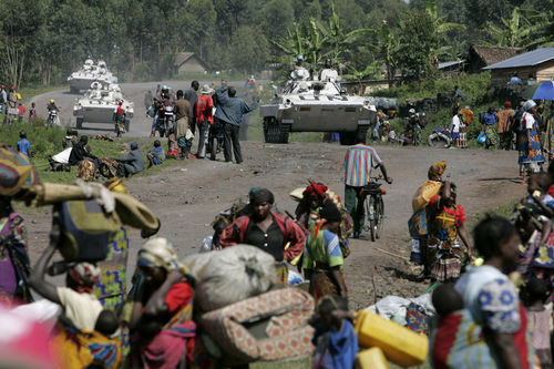United Nations peacekeepers in tanks pass displaced people in the village of Kibati some 12 kilometers north of Goma in eastern Congo, Tuesday, Oct. 28, 2008.