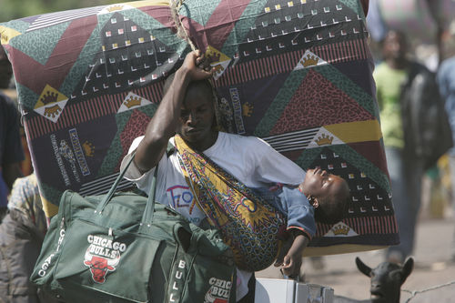 A man carry his son as thousands of displaced people stream into Goma in eastern Congo, Wednesday, Oct. 29, 2008