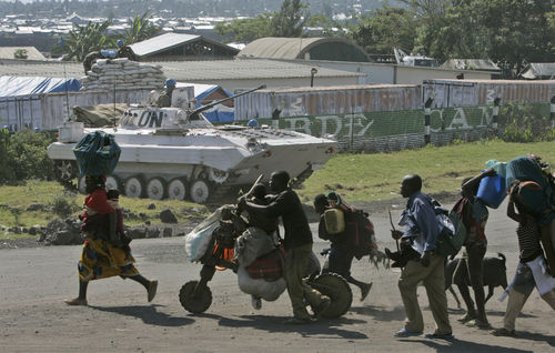 Displaced people run past an United Nations tank outside their headquaters as thousands of displaced people stream into Goma in eastern Congo, Wednesday, Oct. 29, 2008.