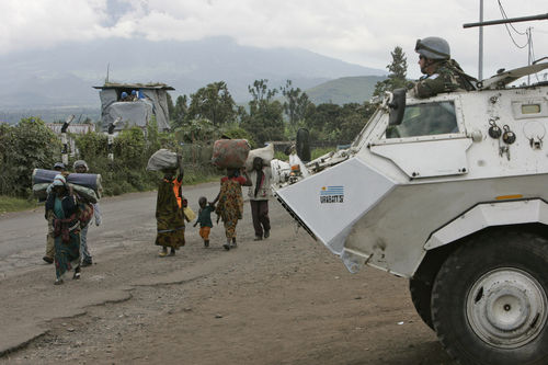 Dislpaced people carrying their belongings walk past an United Nations armoured personel carrier outside their headquaters in Goma in eastern Congo, Thursday, Oct. 30, 2008