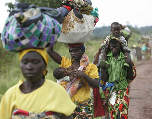 Displaced people walk on a road as they return home, Sunday, Nov. 2, 2008 in Kibumba north of Goma in eastern Congo.