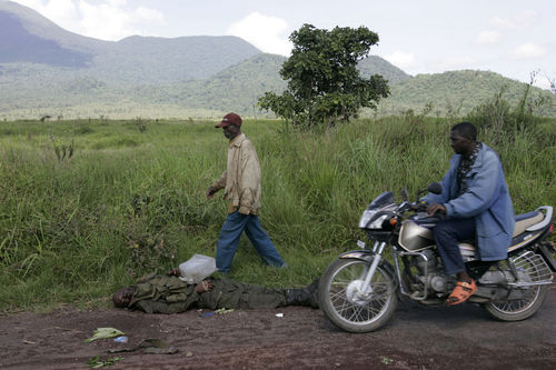 People walk past the body of a Congolese soldier, Friday , Oct. 31, 2008 near Kibumba some 40 kilometers north of Goma in eastern Congo.