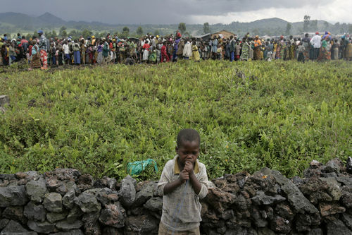 A young boy stand near a line of people waiting to receive high energy biscuits at an at a clinic of the International Medical Corps at a displaced people's camp, Tuesday, Nov. 4, 2008 in Kibati north of Goma in eastern Congo.