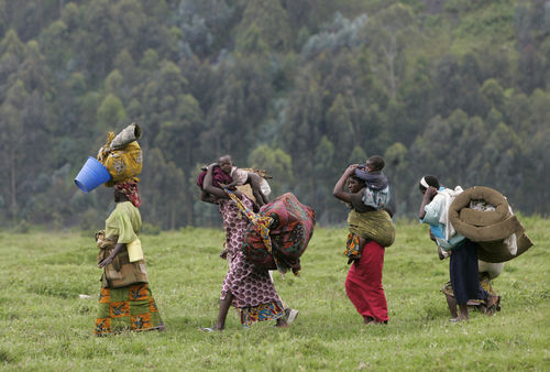 Displaced people walk through a filed as they return home, Sunday, Nov. 2, 2008 in Kibumba north of Goma in eastern Congo.