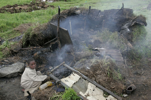 A dsiplaced child sit in the ruins of a hut that was destroyed during fighting last week after displaced peole evacuated the Kibumba displaced people's camp, Sunday , Sept. 2, 2008 in Kibumba north of Goma in eastern Congo.
