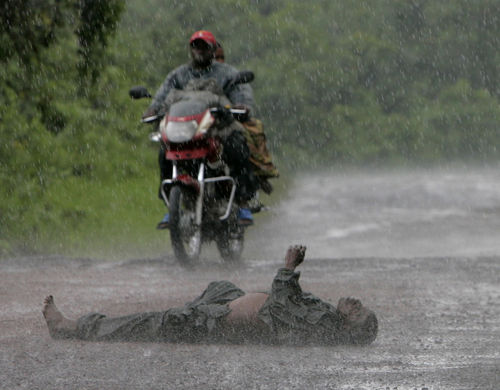 The body of a goverment soldier killed in fighting during the night is seen in the road on the front line, Wednesday, Nov. 12, 2008 near Kibati just north of Goma in eastern Congo.