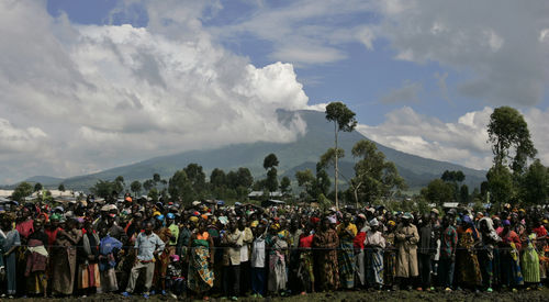Displaced people line up to receive non food items from the Red Cross with Nyiragongo volcano smoking in the background, Wednesday, Nov. 12, 2008 in Kibati just north of Goma in eastern Congo.