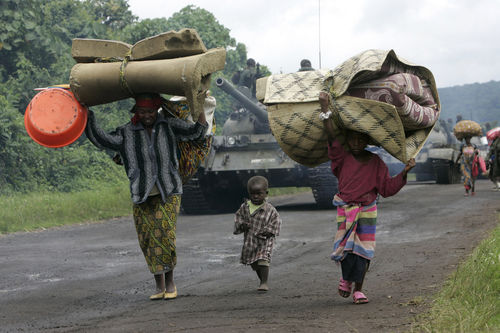 People run past an convoy of Congolese army tanks as they  flee fighting, Monday, Oct. 28, 2008 near Kibumba some 40 kilometers north of Goma in eastern Congo
