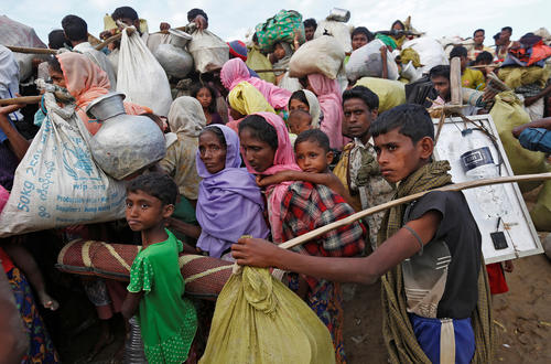 Rohingya refugees make their way towards a refugee camp after crossing the Naf river at the Bangladesh-Myanmar border in Palang Khali, near Cox's Bazar