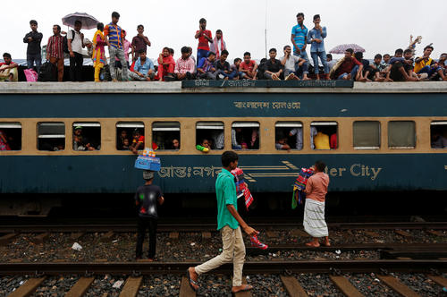 People sit atop of an overcrowded passenger train as they travel home to celebrate Eid al-Fitr festival, which marks the end of the Muslim holy fasting month of Ramadan, at a railway station in Dhaka