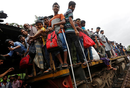 People stand on an engine of an overcrowded passenger train as they travel home to celebrate Eid al-Fitr festival, which marks the end of the Muslim holy fasting month of Ramadan, at a railway station in Dhaka