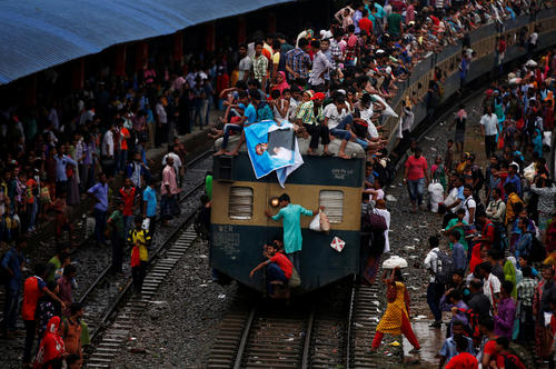 People sit atop an overcrowded passenger train as they travel home to celebrate Eid al-Fitr festival, which marks the end of the Muslim holy fasting month of Ramadan, at a railway station in Dhaka
