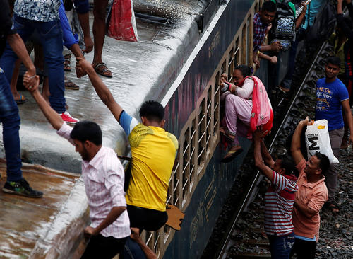 People try to board an overcrowded passenger train as they travel home to celebrate Eid al-Fitr festival, which marks the end of the Muslim holy fasting month of Ramadan, at a railway station in Dhaka