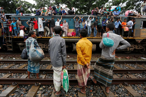 People sit atop and stand outside on an engine of an overcrowded passenger train as they travel home to celebrate Eid al-Fitr festival, which marks the end of the Muslim holy fasting month of Ramadan, at a railway station in Dhaka