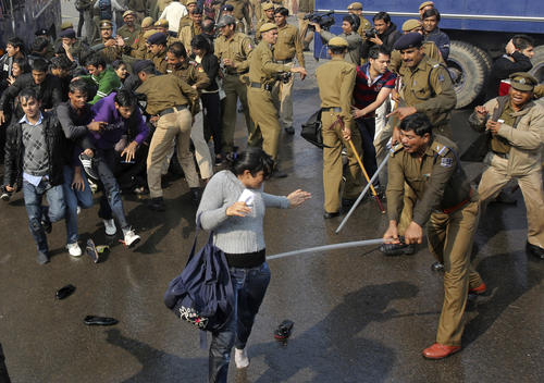 A policeman wields his baton against a demonstrator near the presidential palace during a protest rally in New Delhi