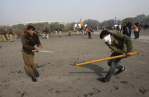A police officer and a demonstrator scuffle near the presidential palace during a protest rally in New Delhi