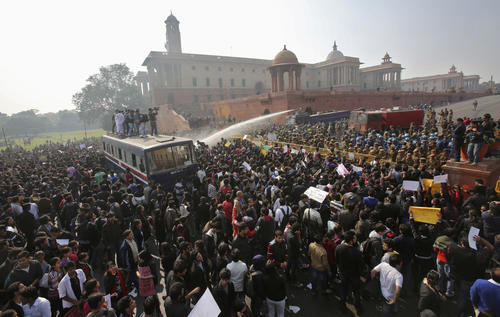 Demonstrators are hit by police water cannon as they shout slogans near the presidential palace during a protest rally in New Delhi