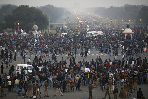 Demonstrators run as they are chased away by police during a protest rally near the presidential palace in New Delhi