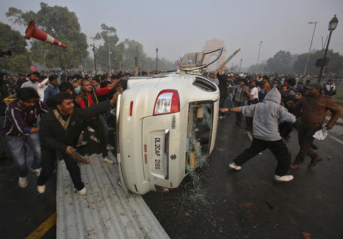 Demonstrators overturn a government vehicle in front of the India Gate during a protest in New Delhi