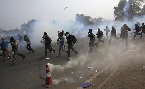 Demonstrators run for cover after police released tear gas to disperse them in front of the India Gate during a protest in New Delhi