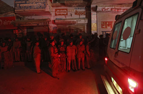 Police stand guard outside residence of rape victim after her body arrived in New Delhi