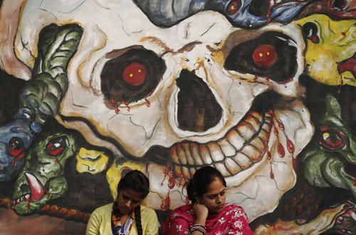 Protesters sit in front of graffiti during a protest to mark the first anniversary of the Delhi gang rape, in New Delhi