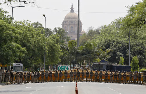 Indian police personnel stand guard to stop supporters of India's main opposition BJP marching towards the parliament house during a protest rally in New Delhi
