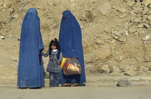 Afghan women clad in burkas wait for transportation on a road in Kabul