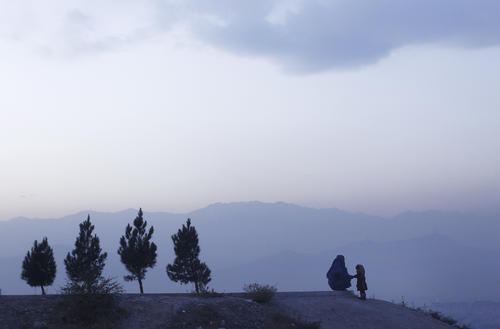 An Afghan woman clad in a burqa sits on a hill top with her daughter in Kabul